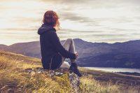Mujer mirando un paisaje sentada en la hierba