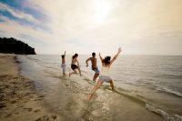 Grupo de amigos corriendo para entrar al agua