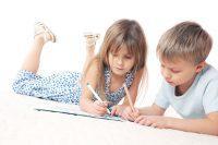 Niño y niña tumbados en el suelo dibujando