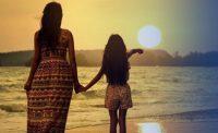 Mujer y niña en la playa mirando puesta de sol