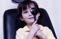 Niña morena en consulta de oftalmología tapándose un ojo
