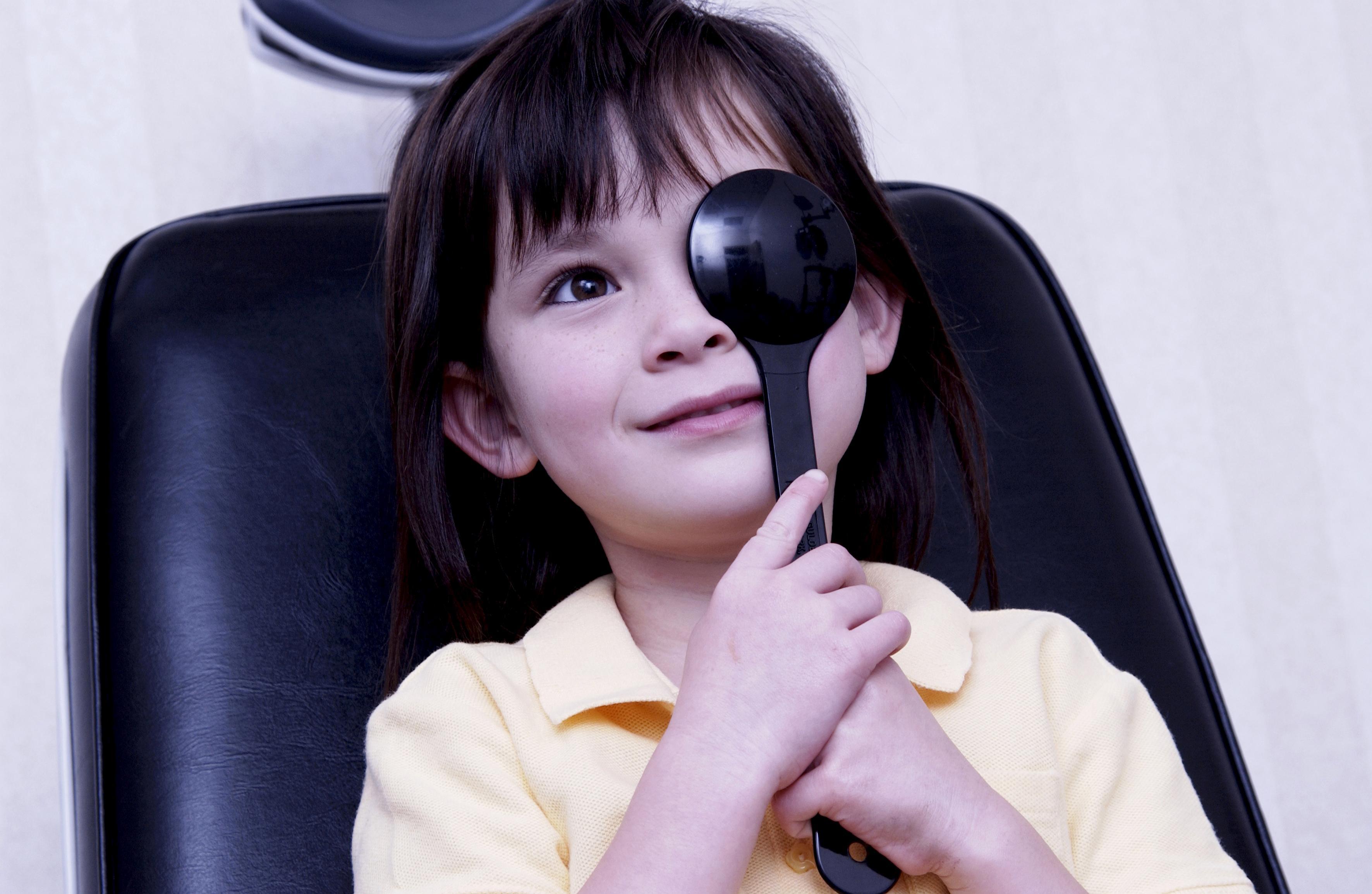 Niño tapándose un ojo durante una revisión oftalmológica