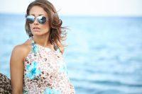 Mujer con gafas de sol y flequillo da la espalda al mar