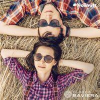Chico y chica con gafas de sol tumbados en la hierba