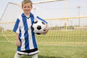 Boy in soccer uniform holding soccer ball by goal