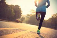 Mujer corriendo de espaldas con zapatillas verdes