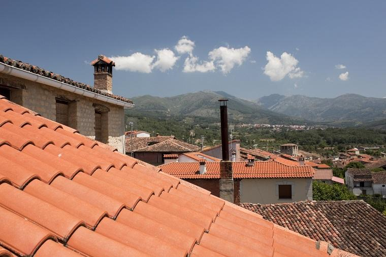 This is a photo that has clouds appearing as though they are leaving the chimney. The photo is taken in Cuacos, Spain and shows traditional houses and the mountains in the distance. This is an optical illusion and has not been digitally altered.