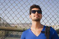 Hombre con camiseta azul y gafas de sol negras