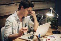 Hombre con gafas en la mano descansa la vista frente al ordenador