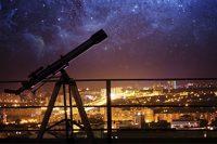 Telescopio frente a ciudad iluminada