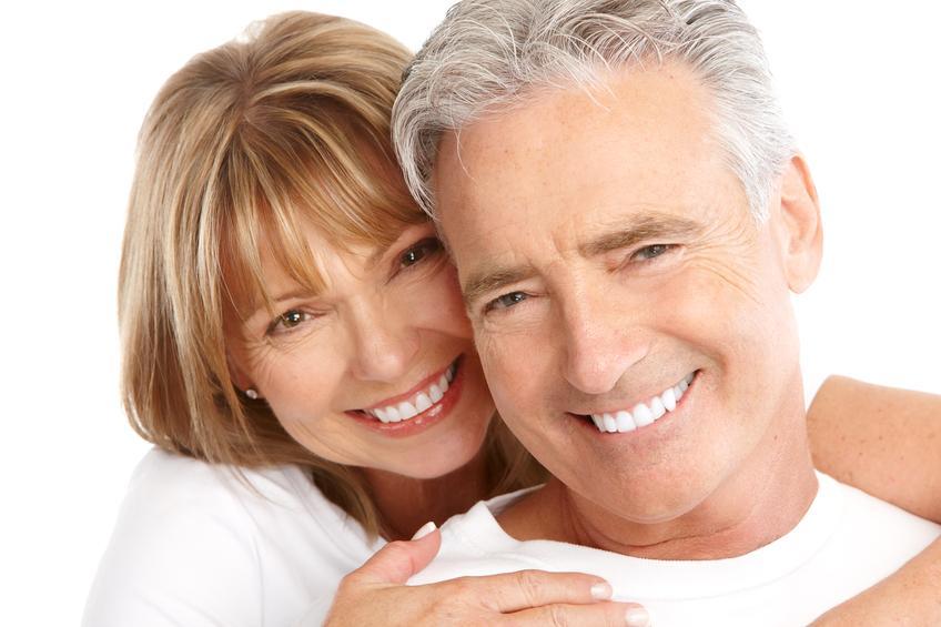 Hombre y mujer vestidos de blanco y sonriendo