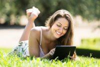 Mujer sonrie mientras lee un ebook al aire libre