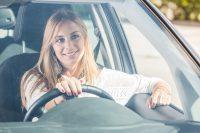 Mujer rubia sonriendo mientras conduce