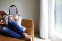 Mujer tumbada en sofá mirando una tablet