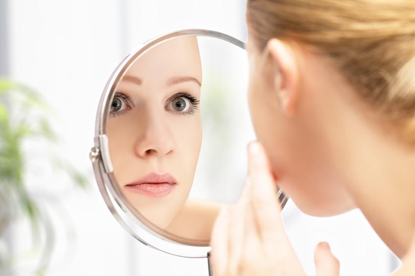 Mujer rubia de ojos verdes mirándose a un espejo