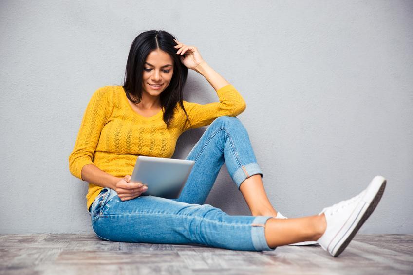 Mujer morena con jersey amarillo leyendo ebook o tablet sentada en el suelo