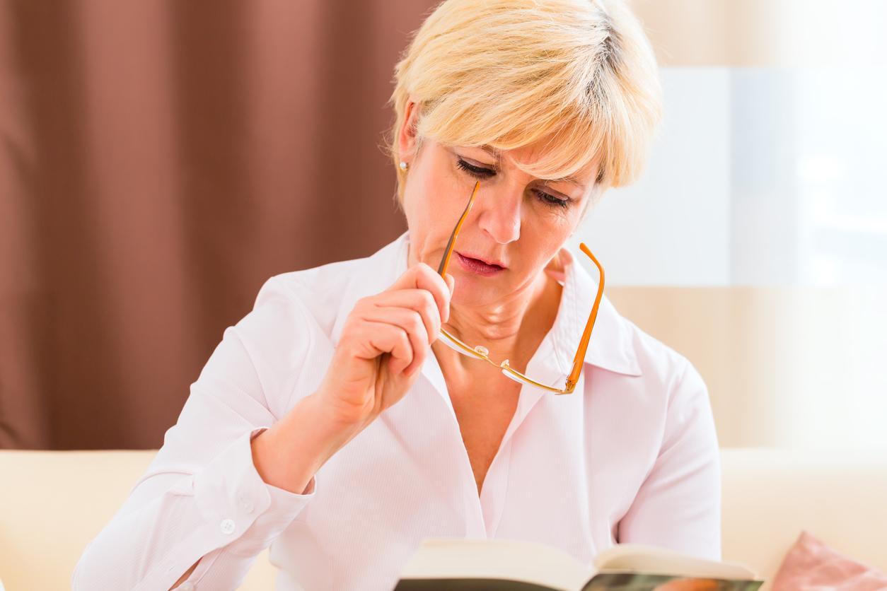 Mujer rubia poniéndose las gafas para leer un libro
