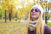 Mujer rubia con gafas de sol, gorro y bufanda en parque otoñal