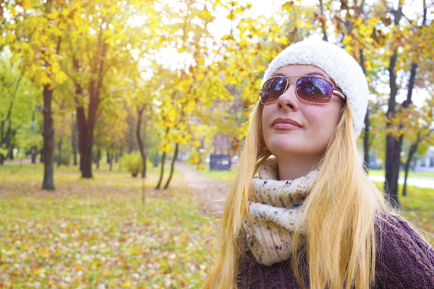 Mujer rubia con gafas de sol en paisaje otoñal