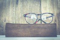 Gafas negras grandes sobre libro marrón y fondo de madera