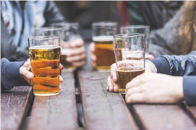 Vasos de cerveza encima de una mesa de madera