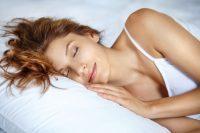 Mujer pelirroja durmiendo en una cama