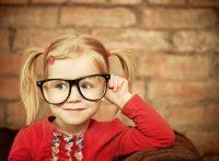 Niña rubia con vestido rojo y gafas grandes