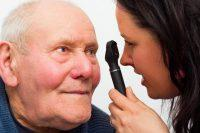 Médico revisa a paciente anciano con oftalmoscopio indirecto