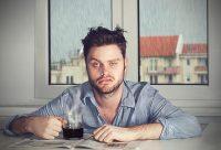 Hombre recién levantado tomándose un café