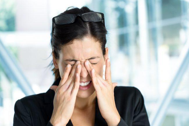 Mujer frotándose los ojos con chaqueta negra y gafas en la cabeza
