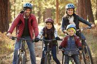 Pareja y dos niños montando en bicicleta por el bosque