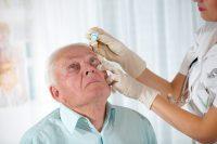 Enfermera con guantes le echa colirio a un paciente