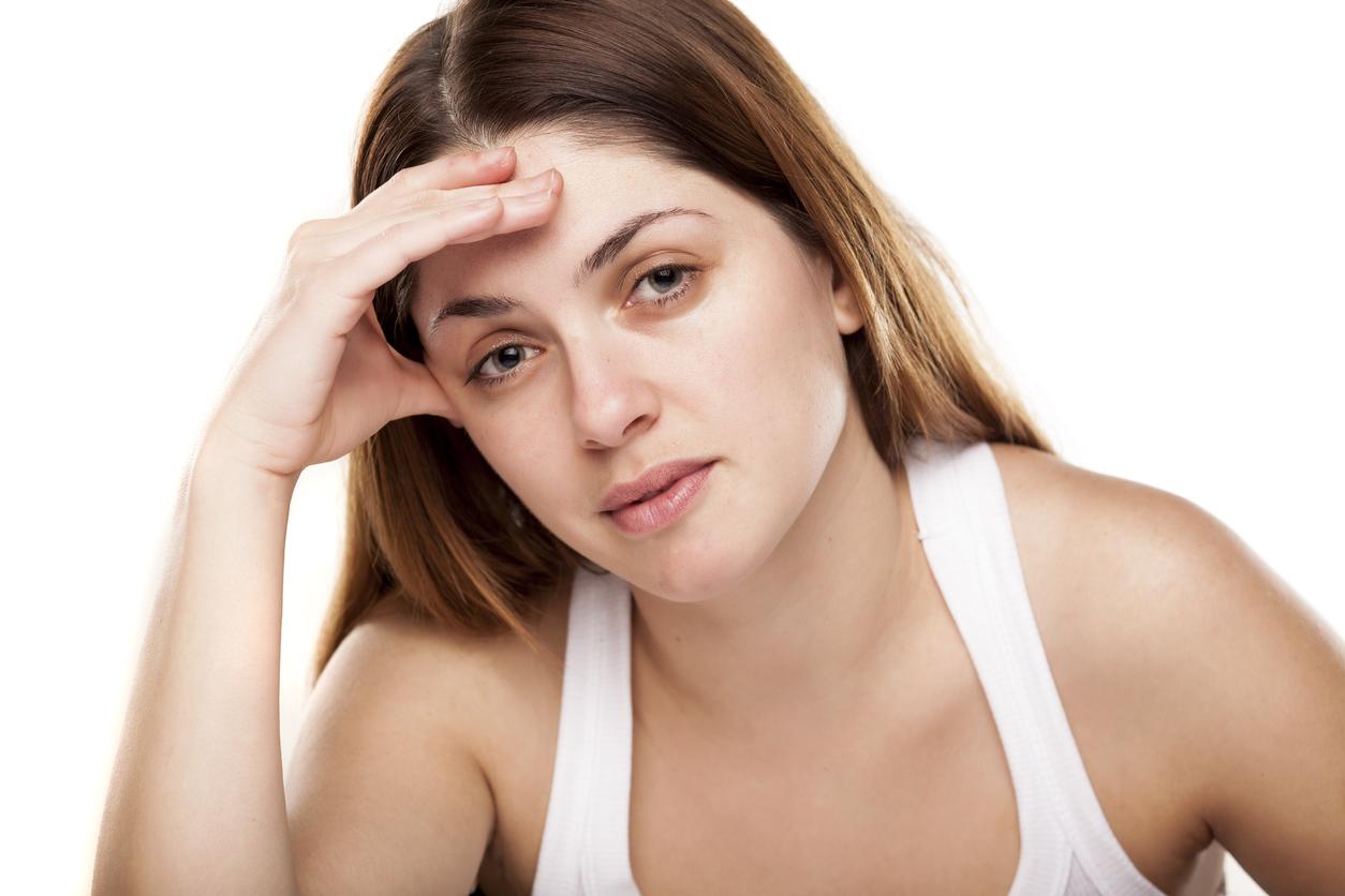 Mujer con camiseta blanca de tirantes y cara de cansada