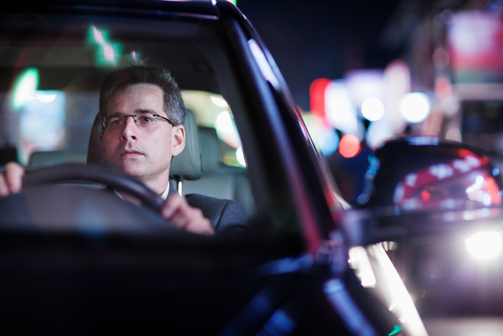 Hombre con gafas conduciendo un coche oscuro