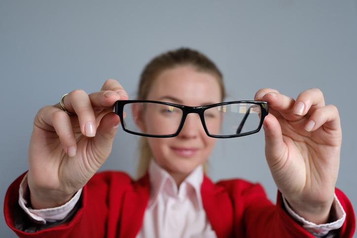 95546ebc6cddc5 Mujer con chaqueta roja enseñando unas gafas negras