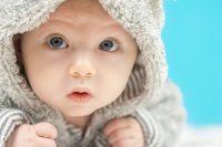 Bebé de ojos azules mira a la cámara