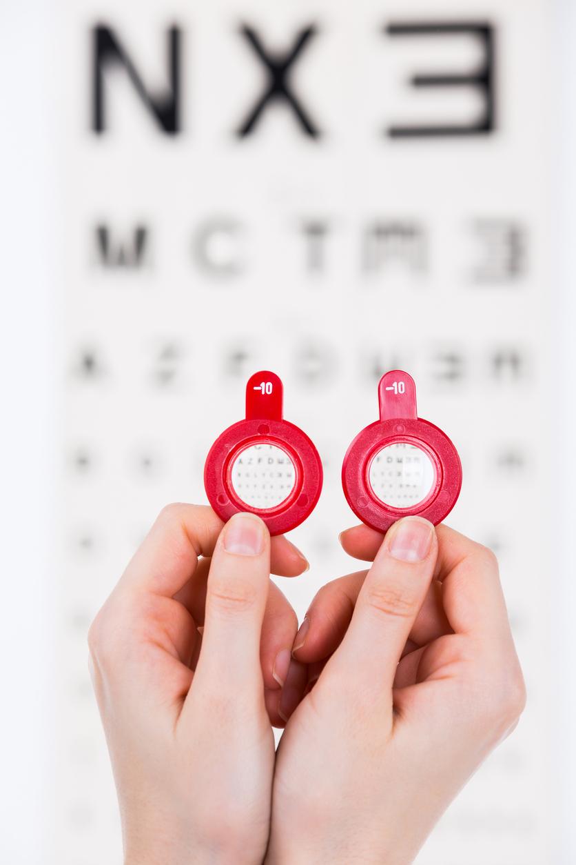 Manos sujetando lentes frente a optotipo