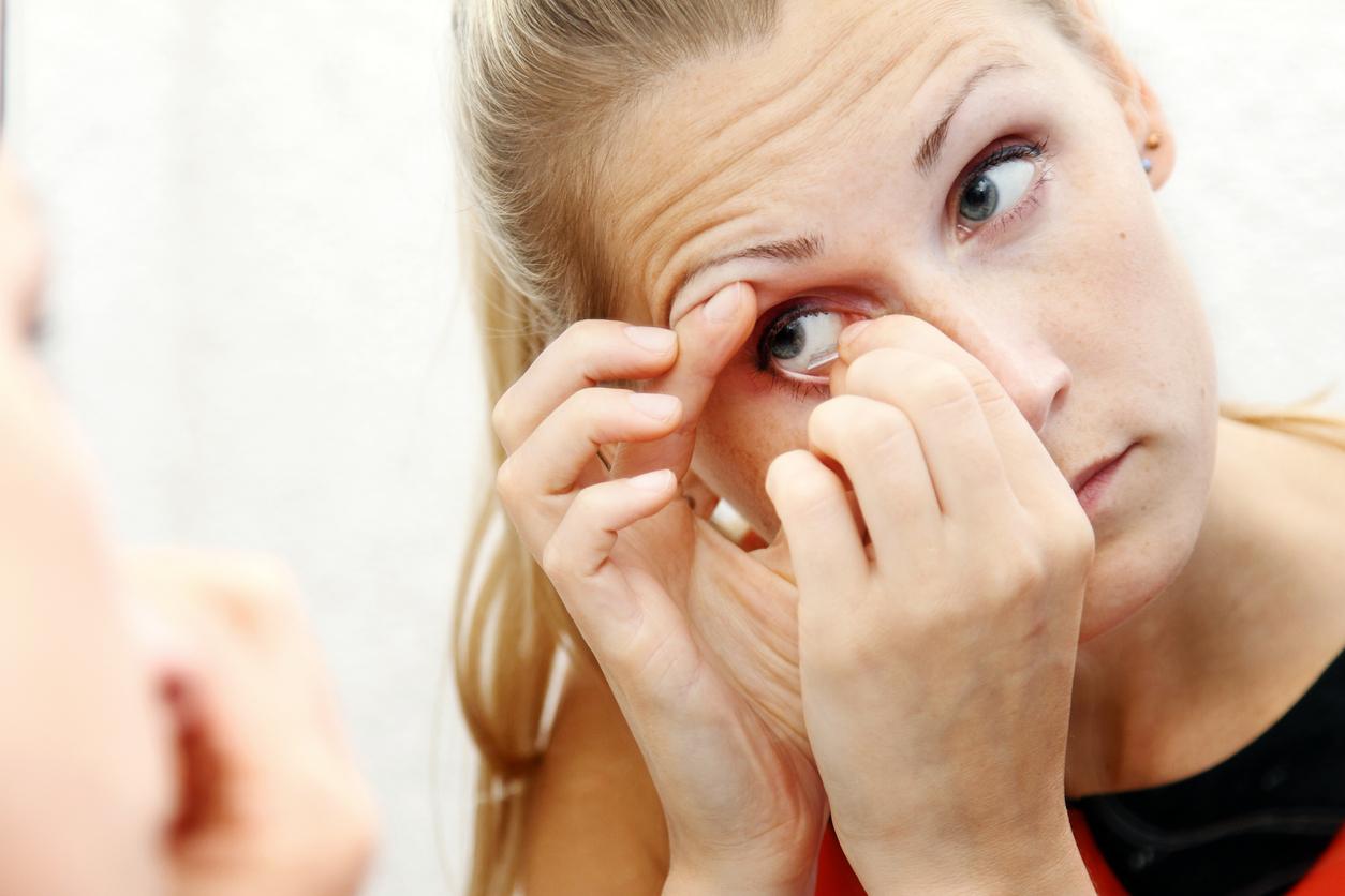 da024028d9e64 Mujer rubia de ojos azules quitándose las lentillas