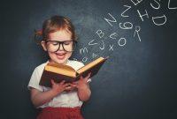 Niña con dos coletas y camiseta blanca leyendo un libro