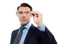 Hombre con traje y camisa azul mirando a través de unas gafas