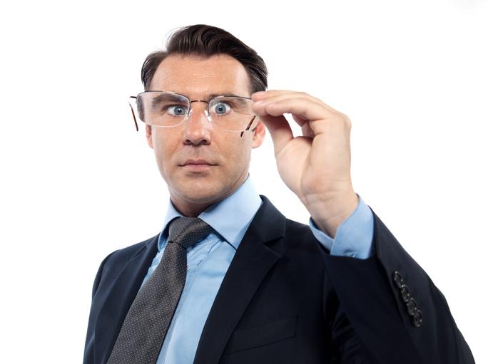 Hombre con traje y corbata mira a través de unas gafas