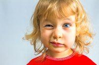 Niño rubio con jersey rojo guiña un ojo