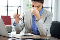 Mujer con chaqueta gris se quita las gafas y se frota los ojos