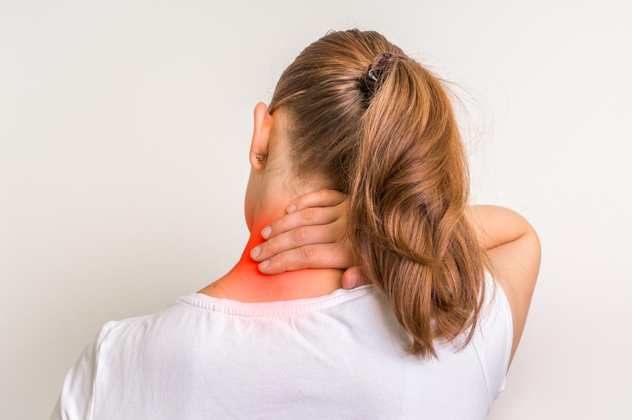 Mujer con camiseta blanca se frota el cuello
