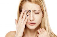 Mujer rubia se frota un ojo