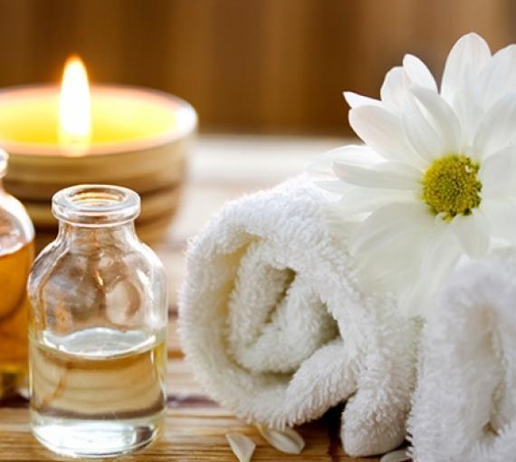 Plan Amigo de Clínica Baviera. Vela encendida, flor, toalla y aceite de masaje