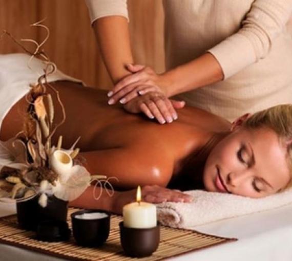 Plan Amigo de Clínica Baviera. Mujer rubia dándose un masaje rodeada de velas