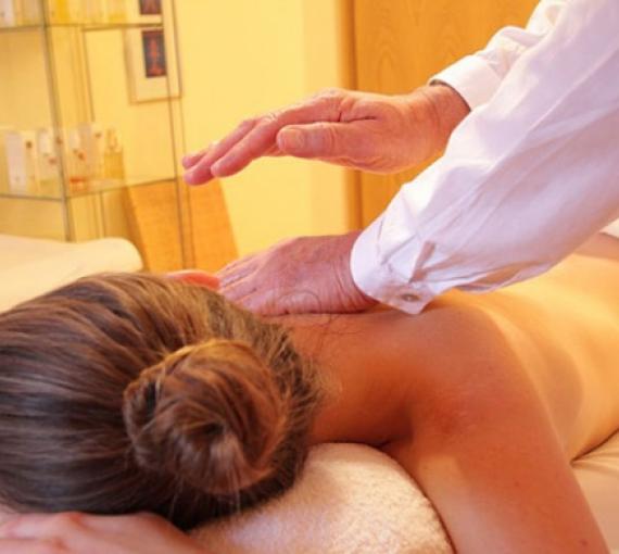 Plan Amigo de Clínica Baviera. Chica haciéndose un masaje y manos masajista